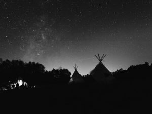 Under. the stars creating stories by a campfire
